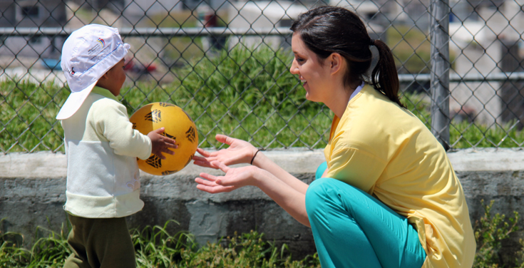 Ecuador team member plays with child