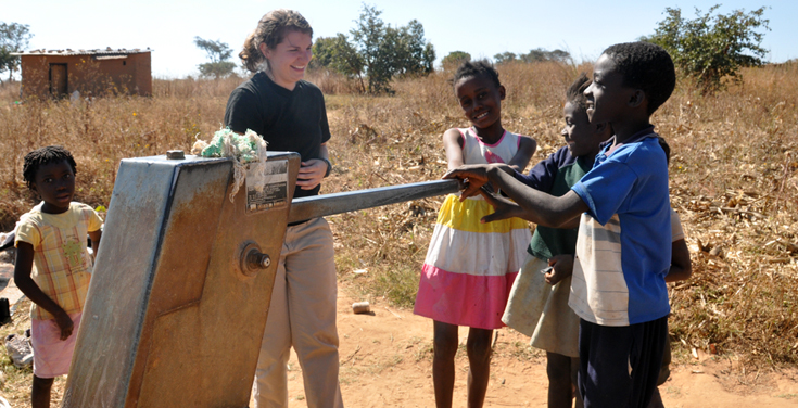 Zambia team member with children at new water pump